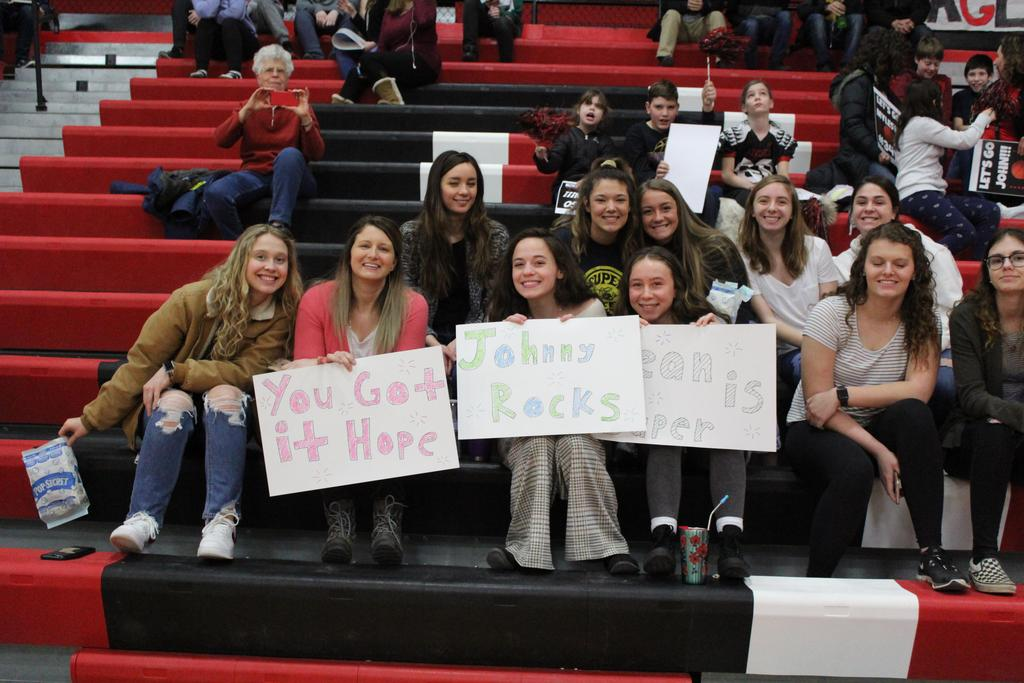 Students holding signs supporting basketball players