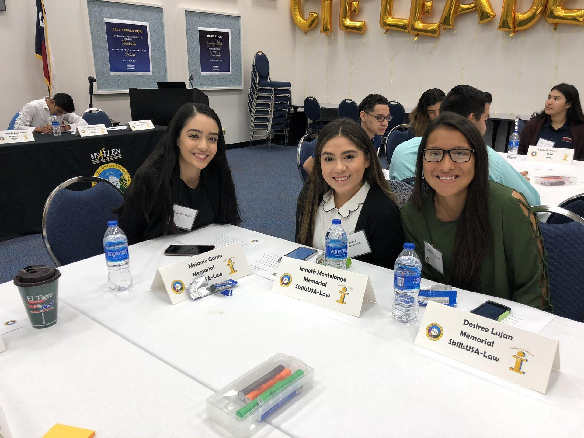 three students sitting around table smiling for the camera