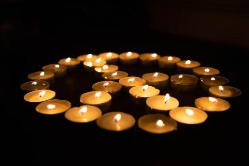 Votive Candles with flames in the shape of the peace sign surrounded by a black background