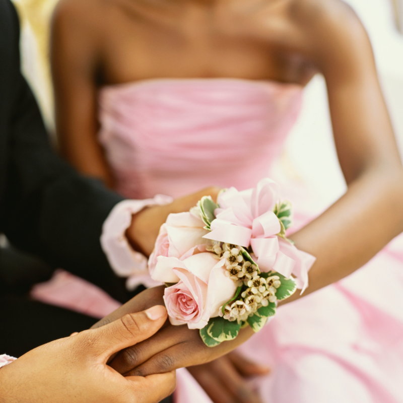 boy putting wrist corsage on girl