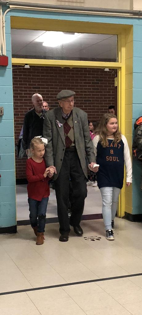 Veteran gentleman enters assembly with two young girls at RCES Veterans Day assembly