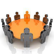 Graphic of people standing around round table.