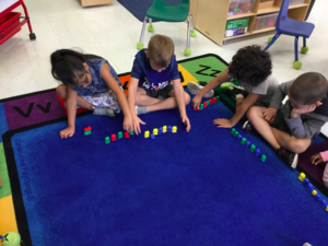 Students sit on rug together with pattern blocks