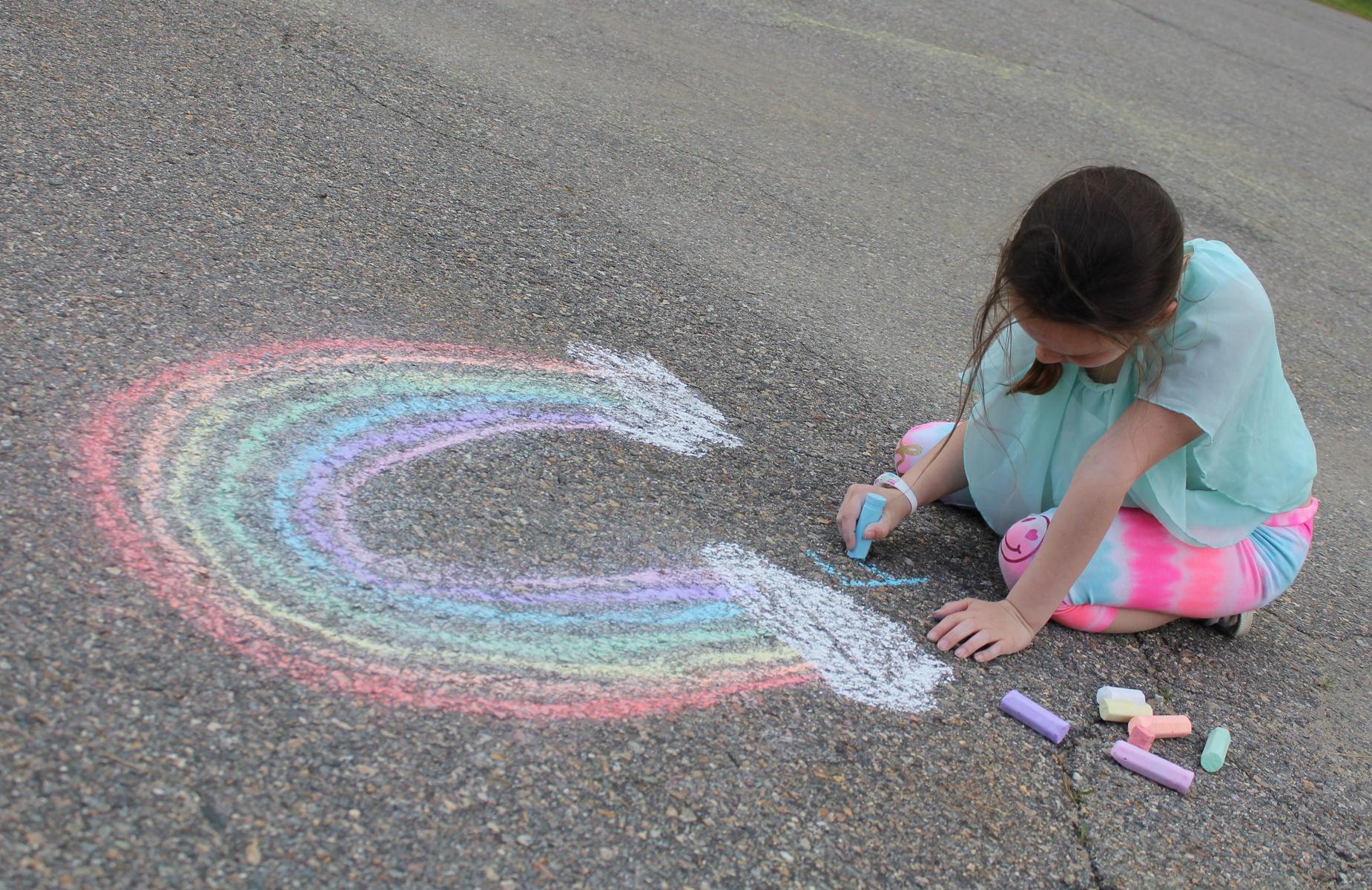 girl drawing a chalk rainbow