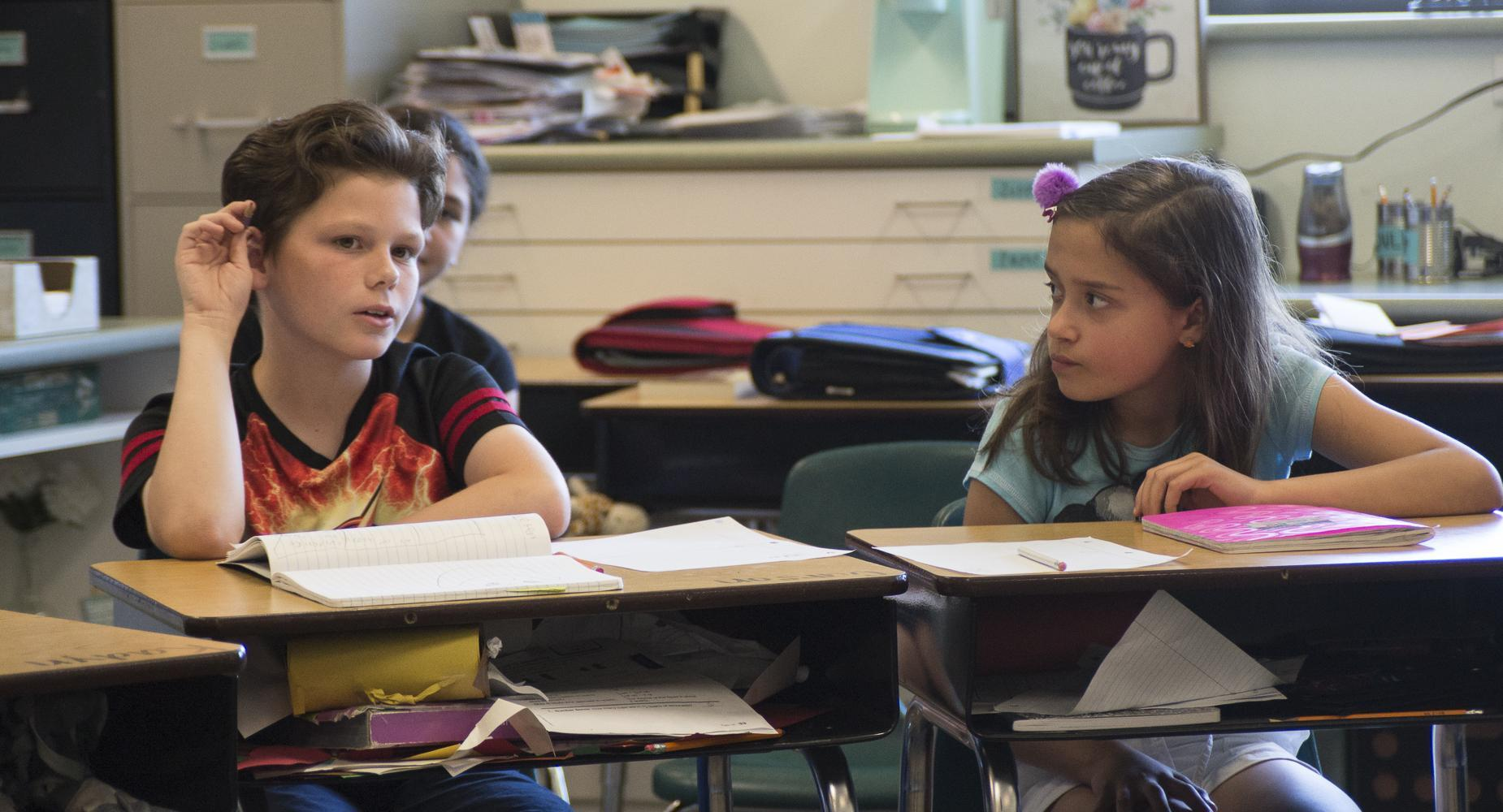 A girl watches a boy answer a question at his desk