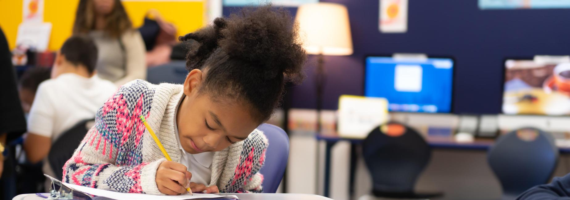 An elementary school student writing at a desk.
