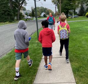 Photo of backs of students as they walk to school
