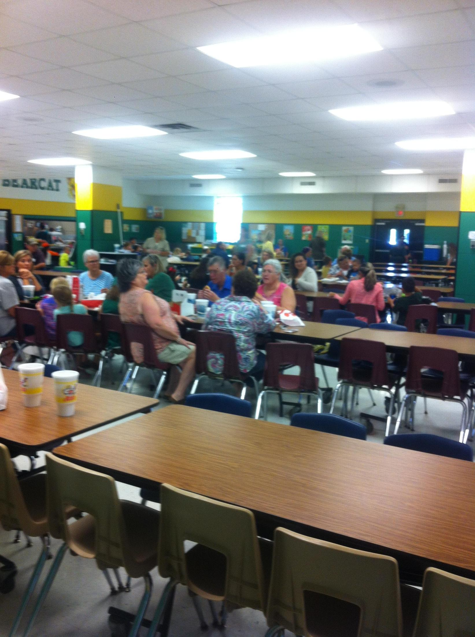 Grandparents sitting at tables for lunch with students.