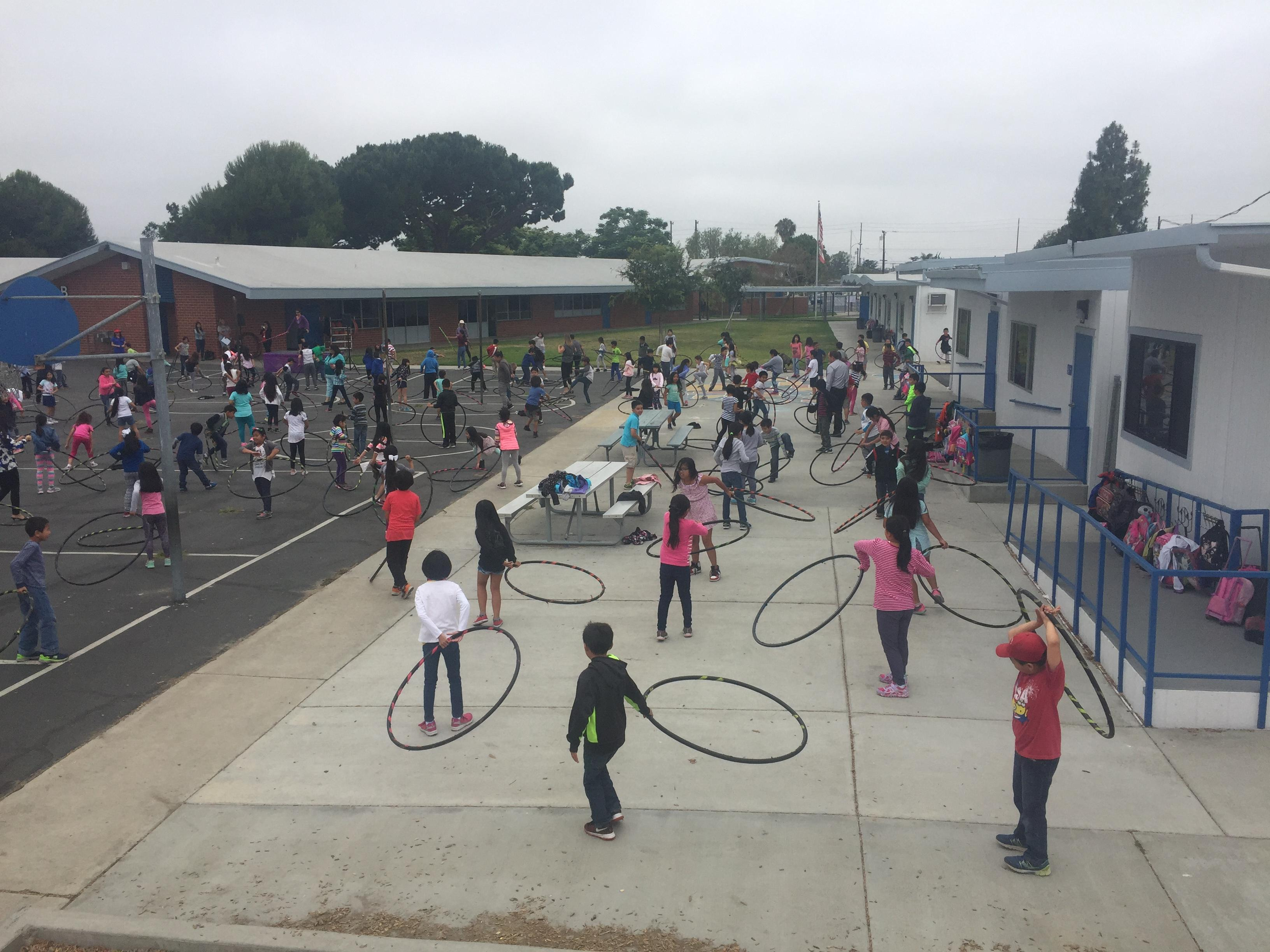 Many students gather on the primary grade's playground using hula hoops during an assembly.