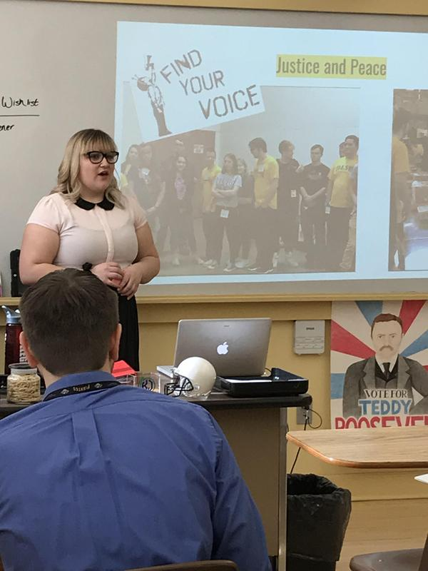 A photo of a student standing in front of a projected display giving a presentation to a room of teachers