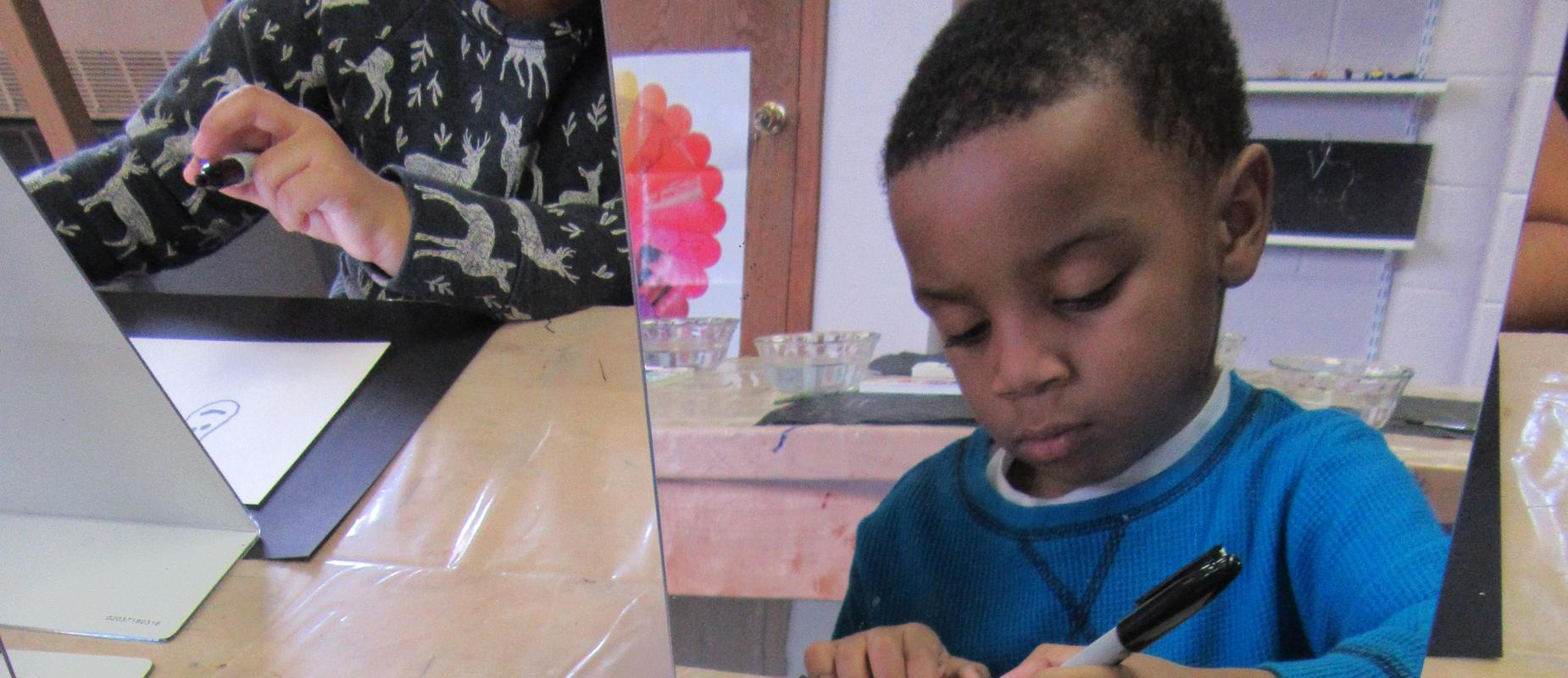 boy drawing a self portrait with marker