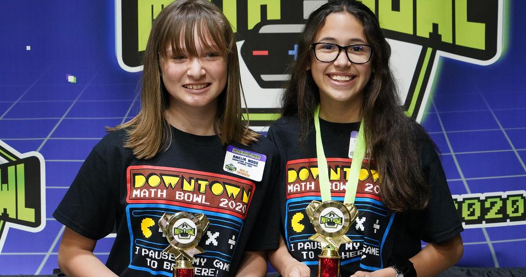 Two students smiling holding a trophy
