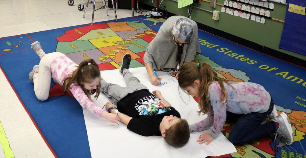 Photo of Tamaques students and 1st grade teacher working on 100th Day activity.