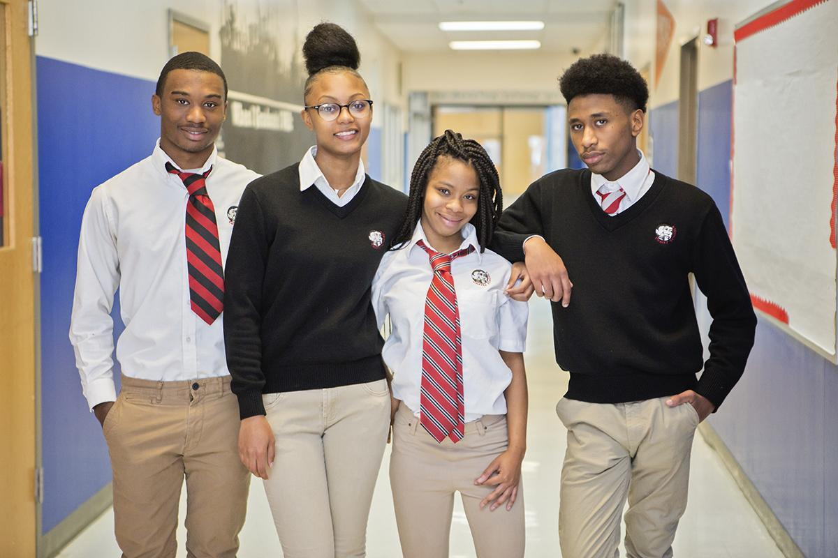 Four students in uniform smiling while in the hallway.