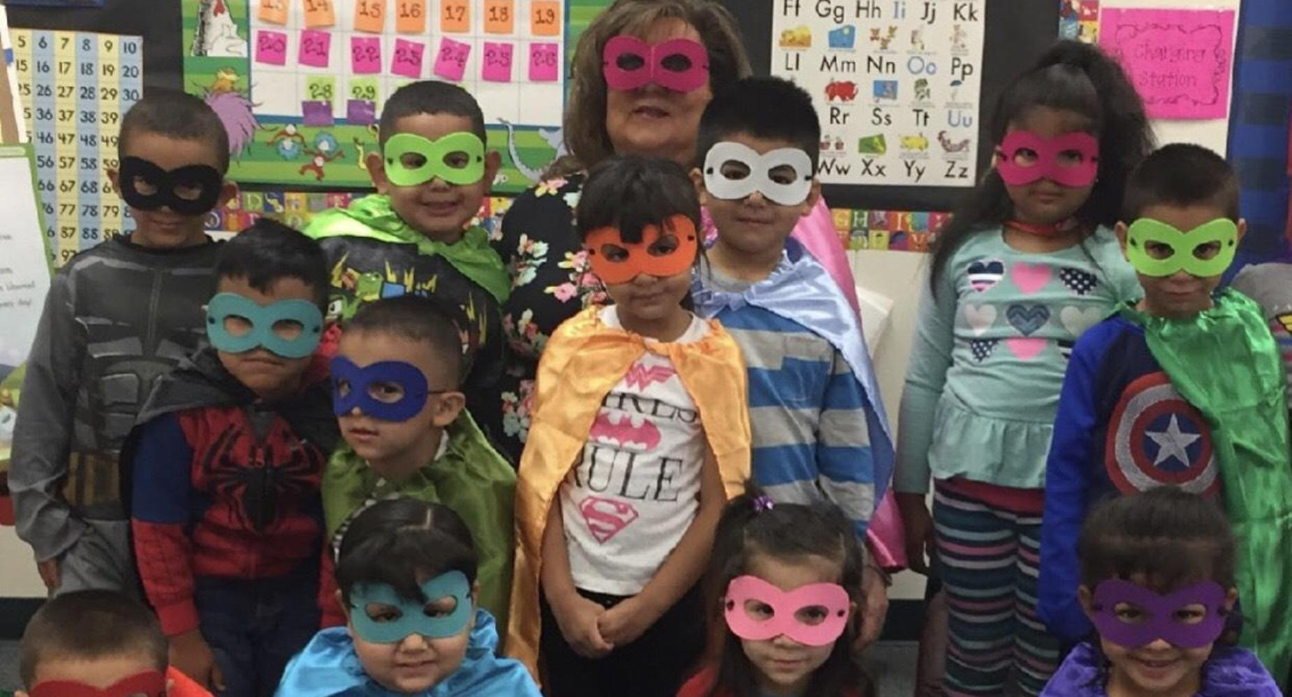 Students with teacher dressed as superheroes.