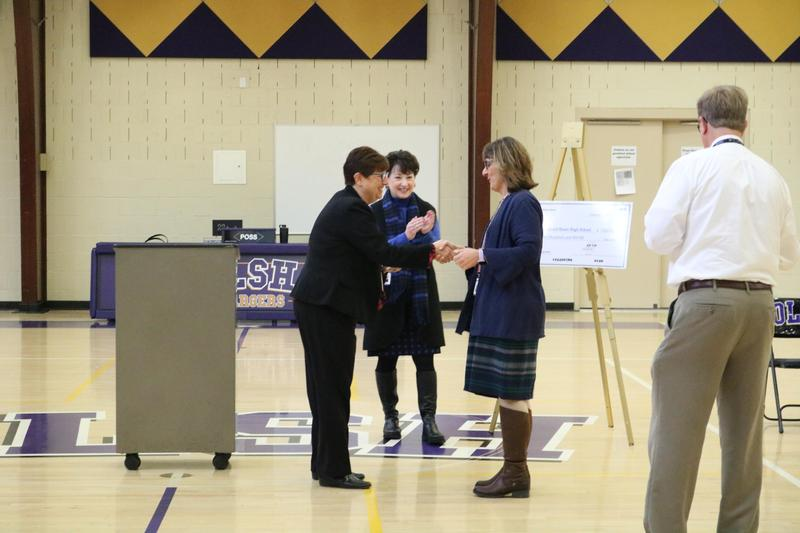 photo of teacher receiving a congratulatory handshake from another woman