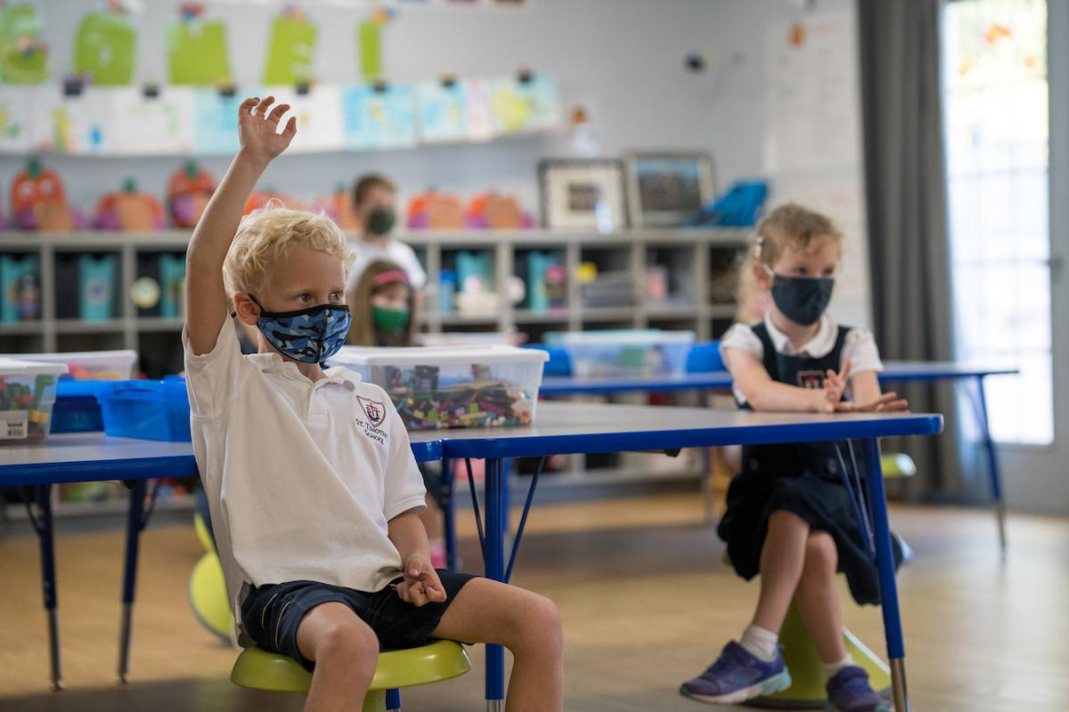 St. Timothy's School kindergarten student with raised hand in classroom