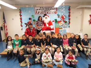 teacher, aide, Santa, and Kindergarten class seated with santa