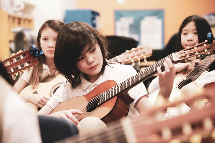 HWIS students in music class with their classical guitars