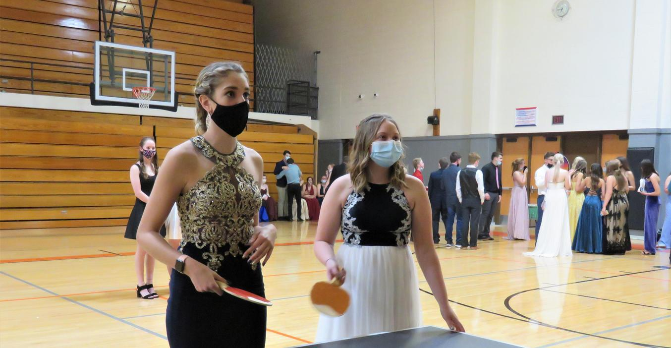Two girls play ping pong at the prom.