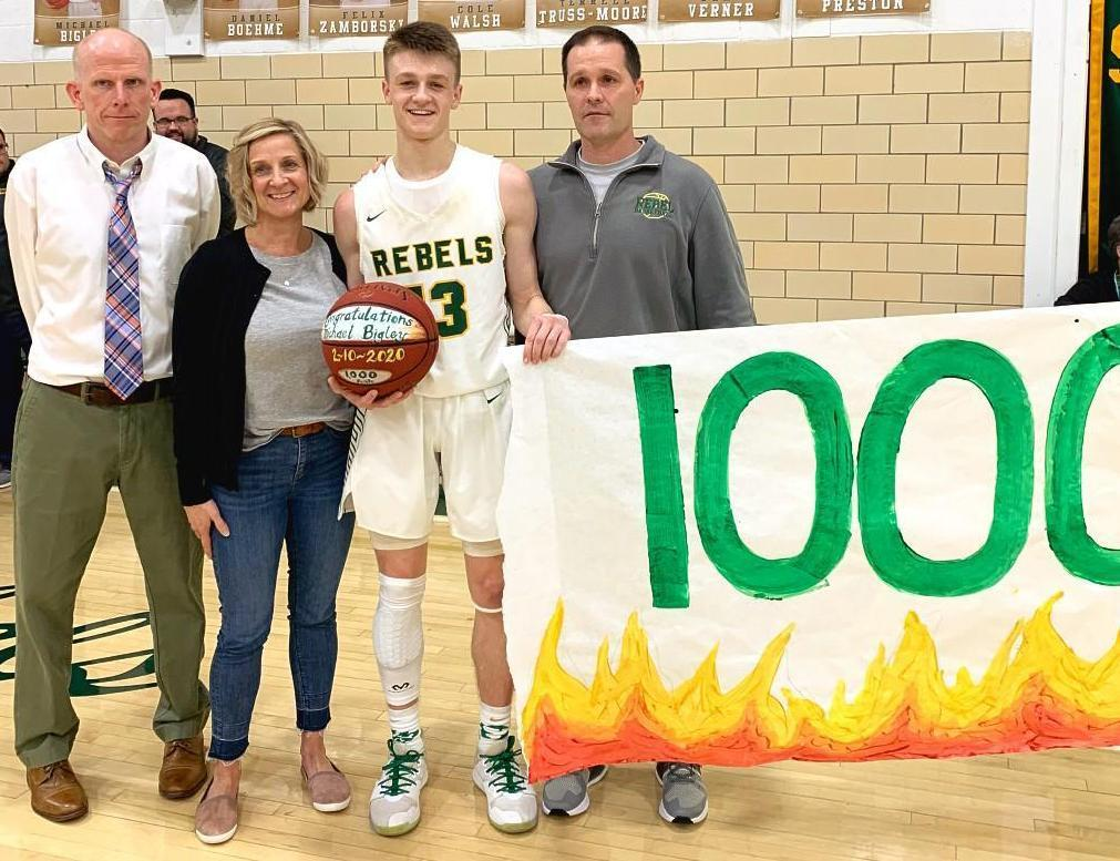 Michael Bigley, '20, poses with his parents and Boys Basketball Coach Mark Walsh, '85, after scoring his 1000th point