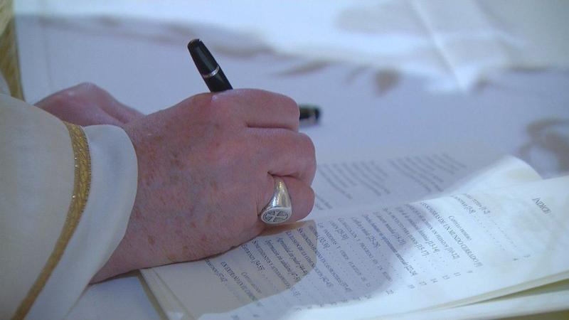 Pope Francis signing the new Encyclical