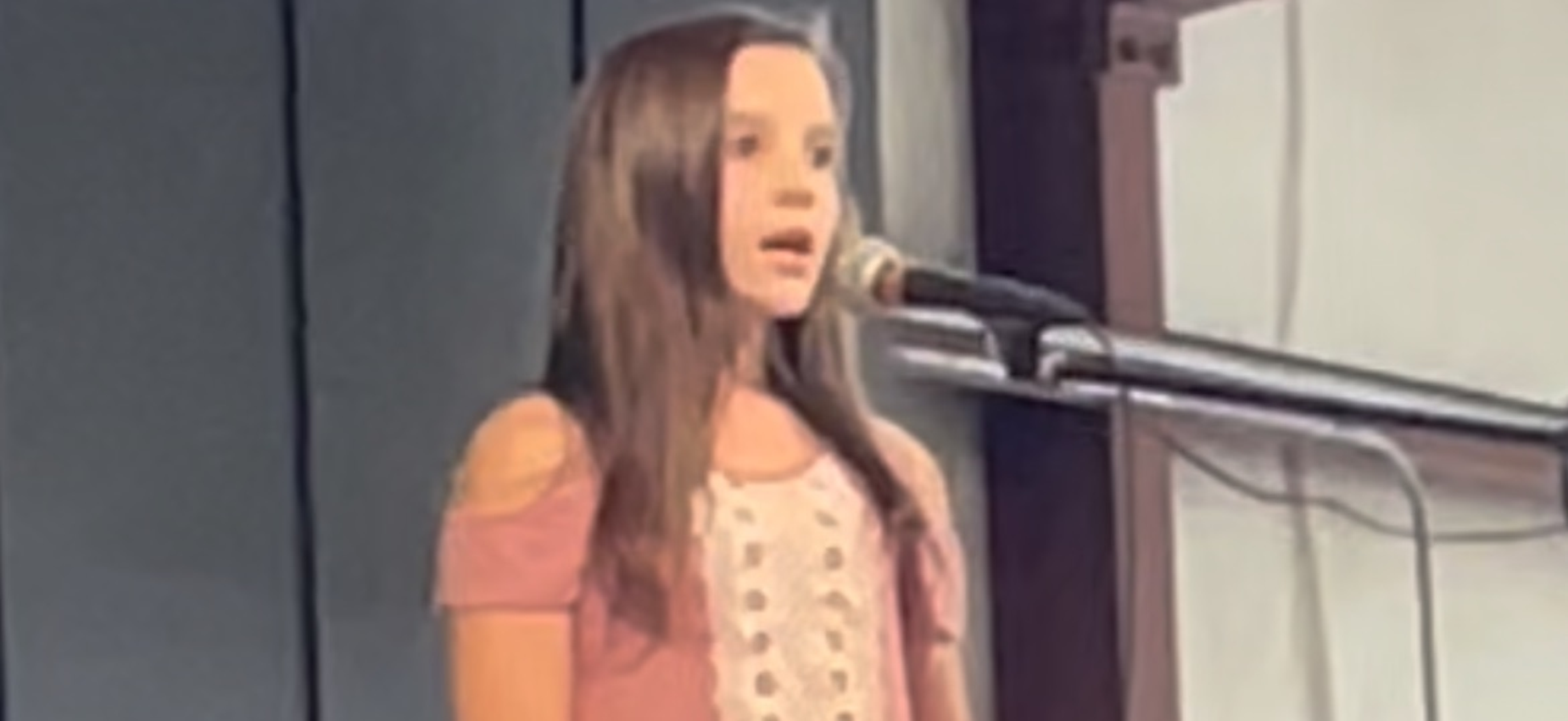 A student sings at a microphone.