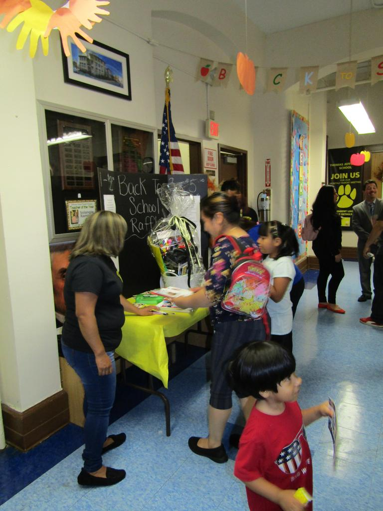 hallway picture of people at the raffle table and talking to principal celebrano