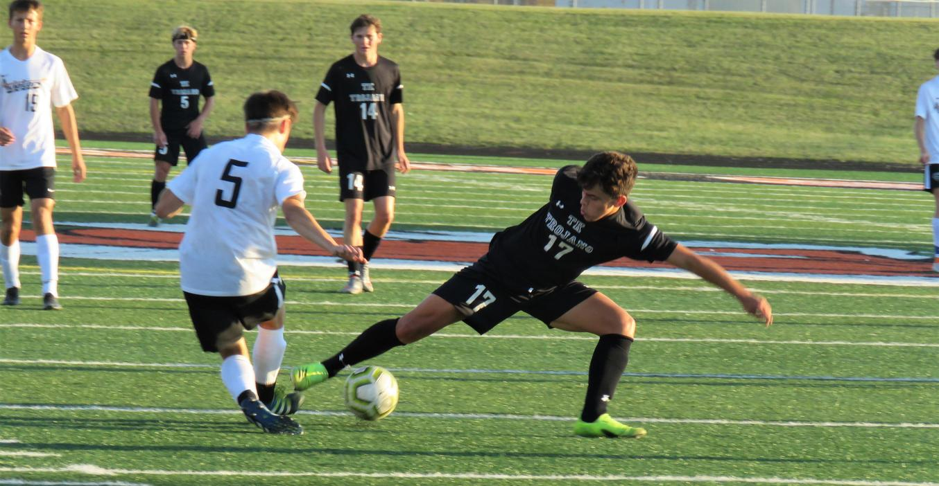 A TK varsity soccer player reaches in for the ball.