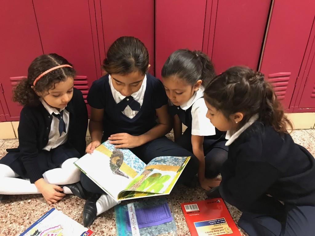 Students reading with an older student