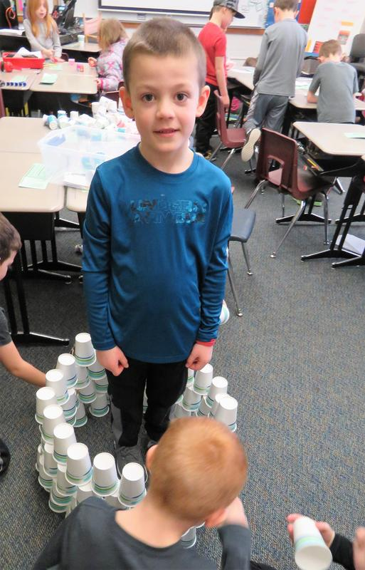 A McFall student stands still while classmates build a wall of paper cups around him.
