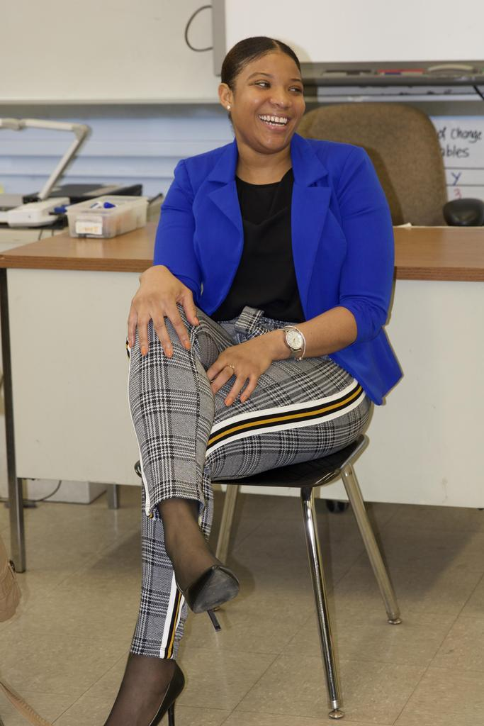 teacher sitting down in chair smiling