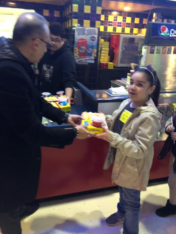 Parent giving a snack box to a girl