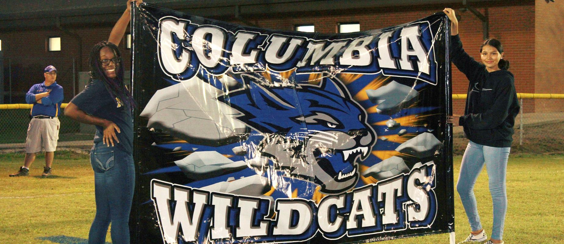 two students holding large Columbia Wildcats banner on football field