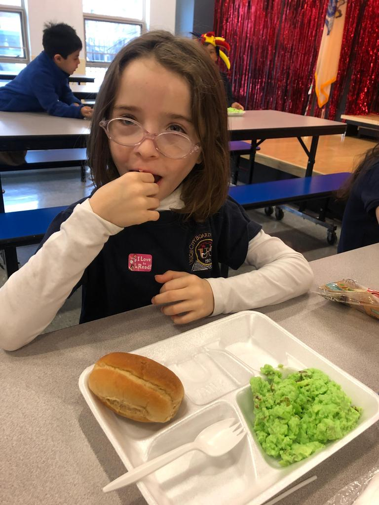 girl with glasses eating a piece of green egg