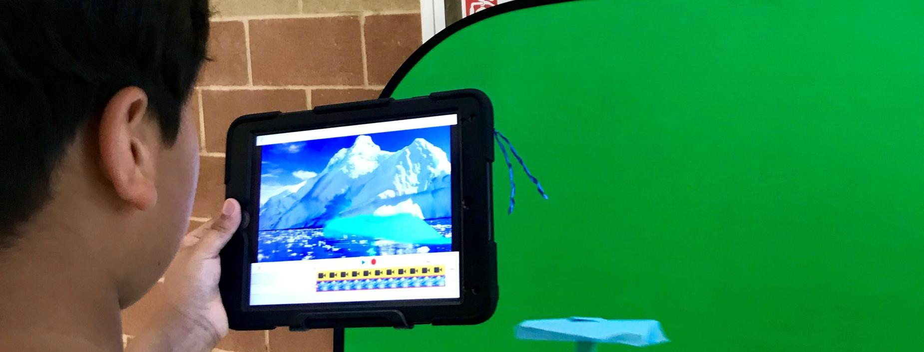 Student uses tablet and green screen.