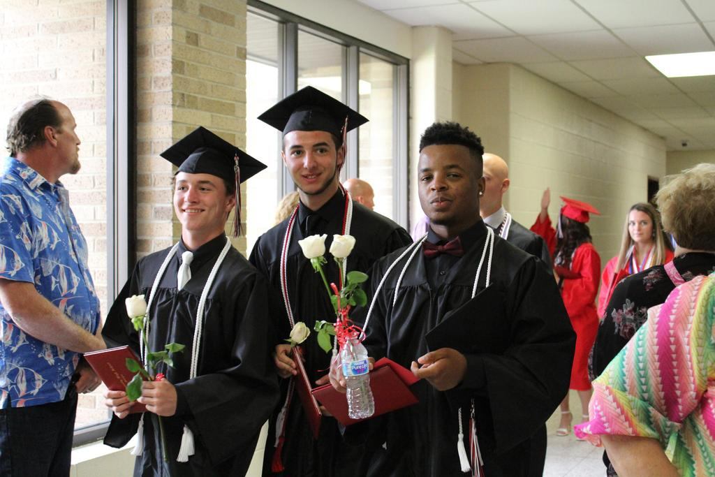 Three smiling male graduates