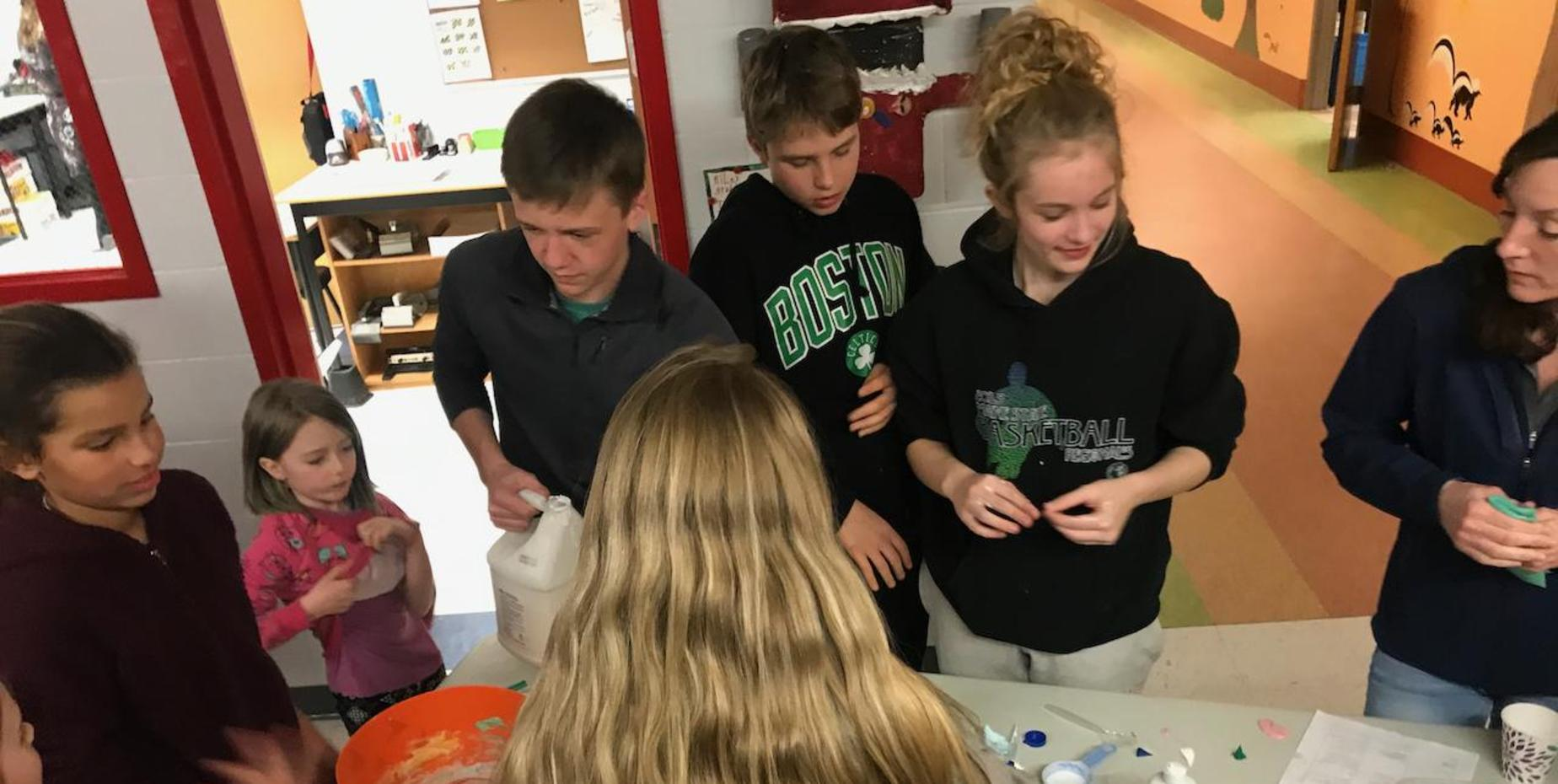 students around table with science experiments