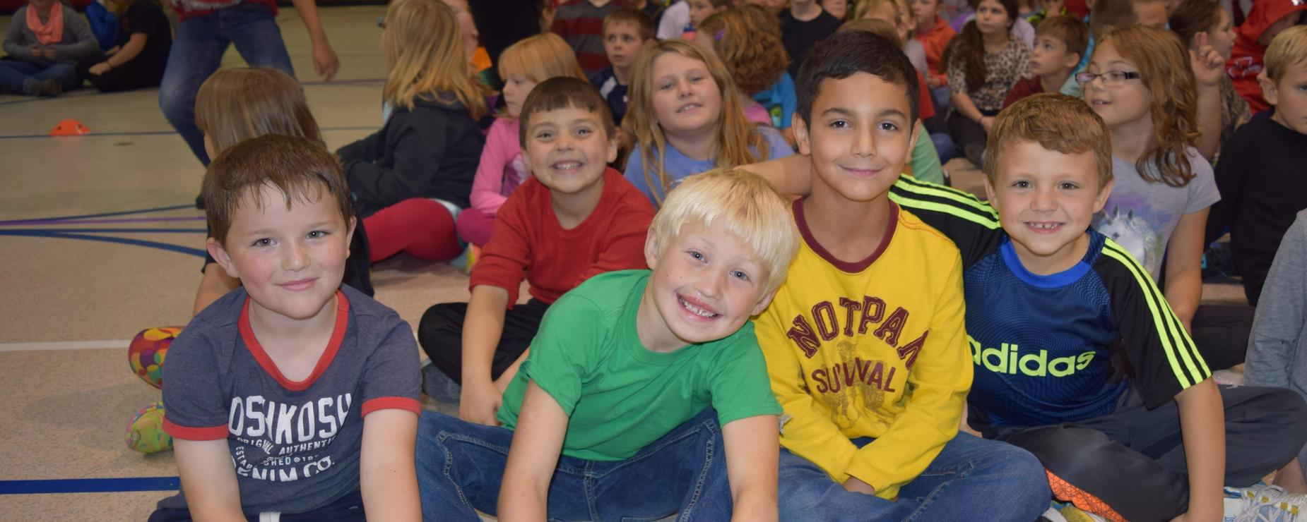 Elementary students smiling together with arms around each other