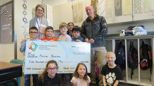 Teacher Norma Pomerlau and Principal Steve LaBau pose with students and a check from the Nampa Schools Foundation.