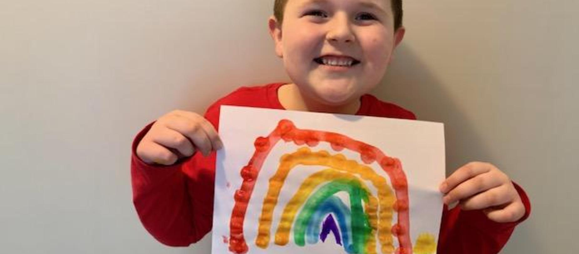 student with rainbow picture