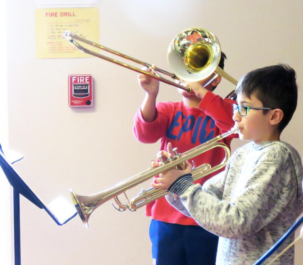 One student plays the trumpet, another a trombone
