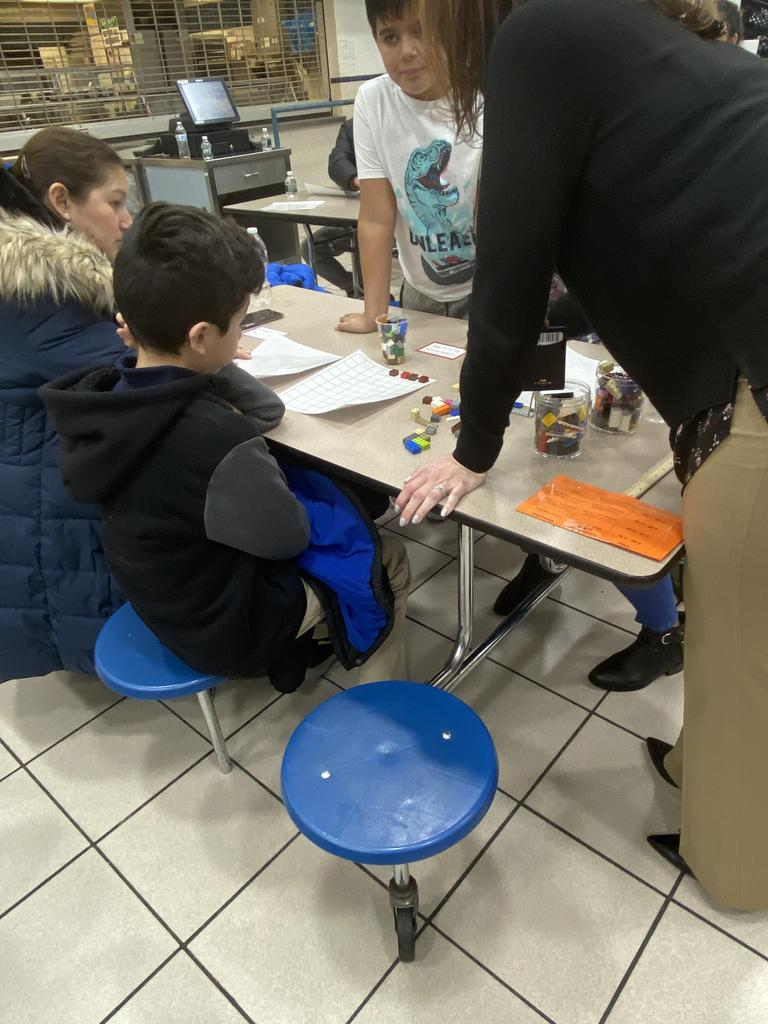 two boys at a table with their mom trying to solve a math problem