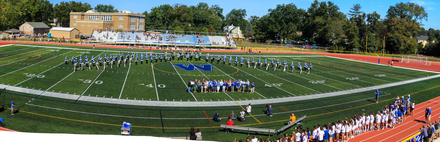 Photo of band, athletes, local dignitaries on Kehler field for re-dedication ceremony.