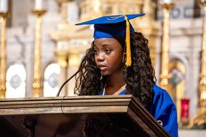 Girl speaks from podium with mic in blue graduation gown with matching hat