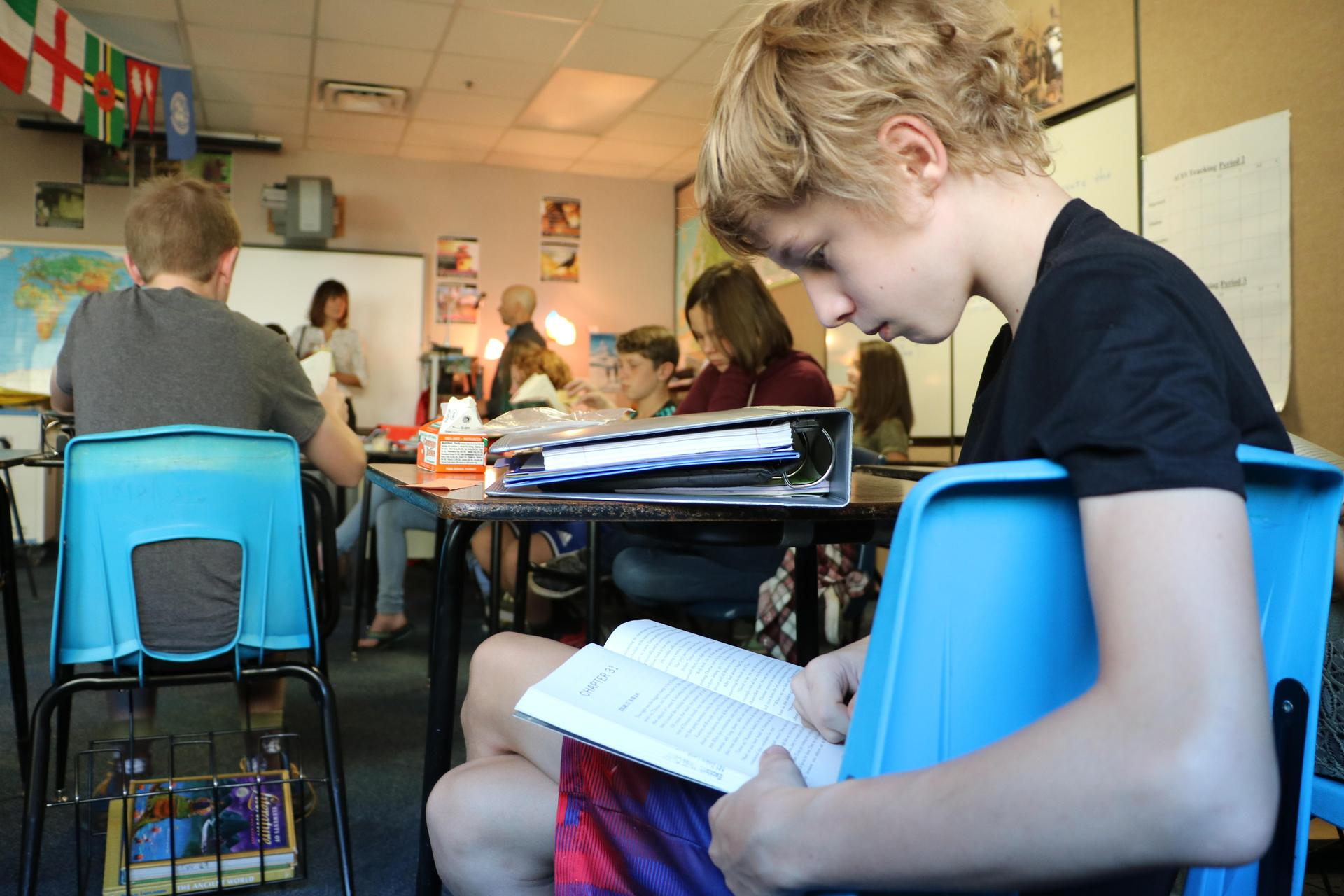 A child reads in a middle school classroom.