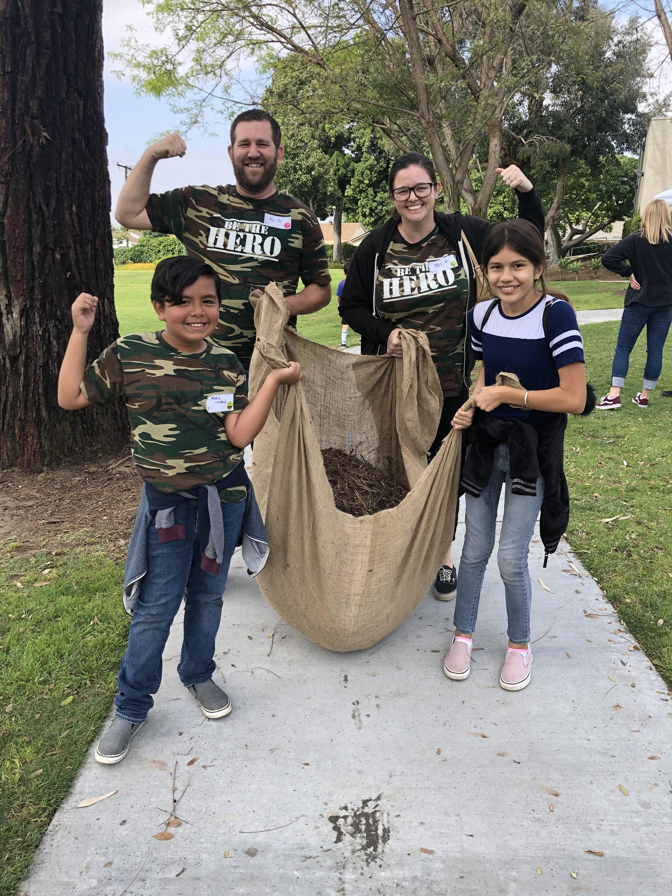 Four Ocean View students and teachers are carrying mulch to help clean up Parnell Park in Whittier.