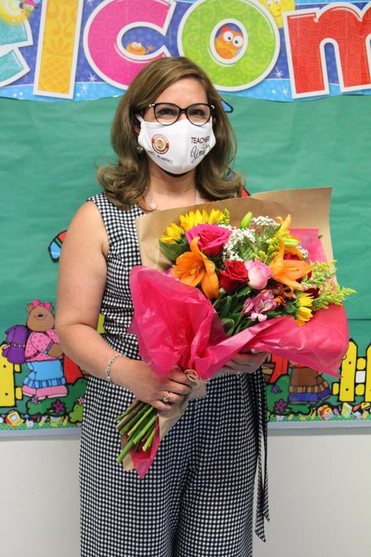 Ms. Romero holding flower bouquet