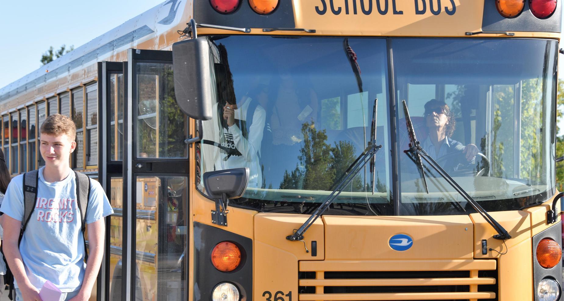Student walking by school bus.