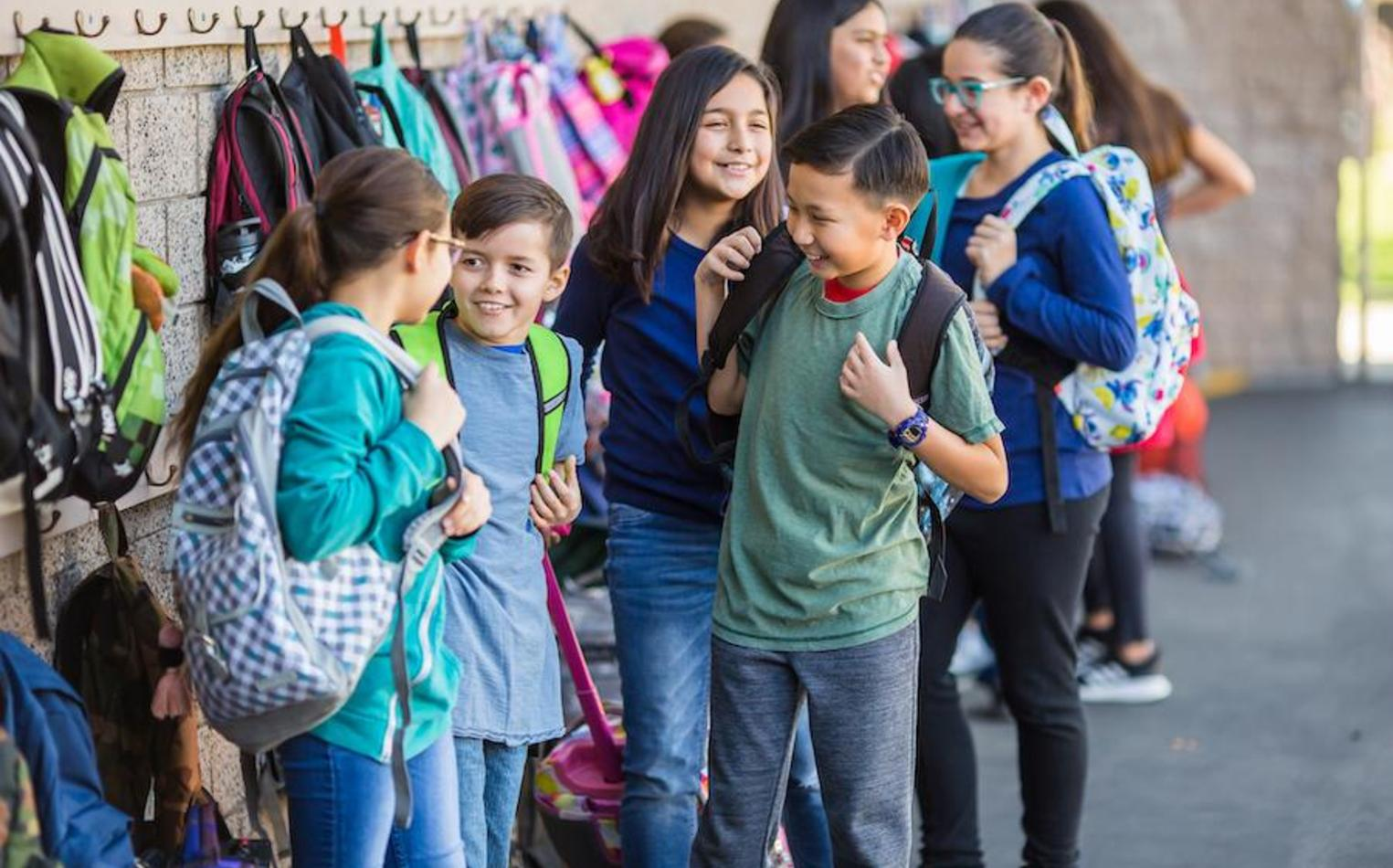 Elementary students getting their backpacks after recess break.